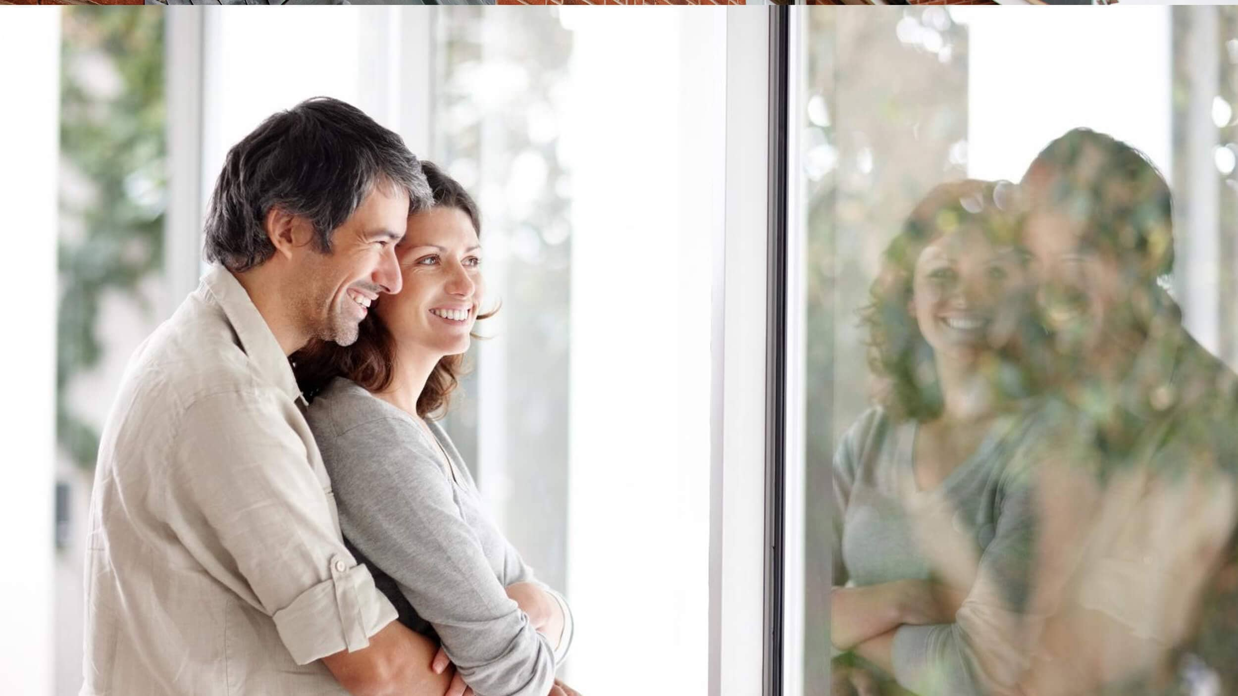 couple hugging and looking at their double glazed windows stock photo